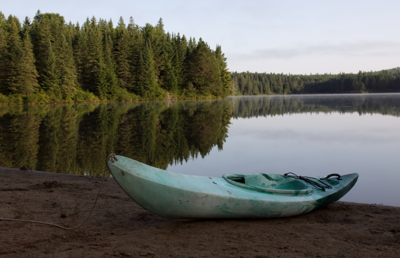 An empty kayak by a lake